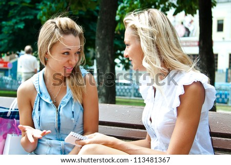 Two beautiful young woman resting on a bench in the park after shopping