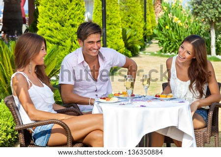 Two beautiful young women and a handsome male friend enjoying a meal in a tropical garden seated at a table together laughing and smiling - stock photo