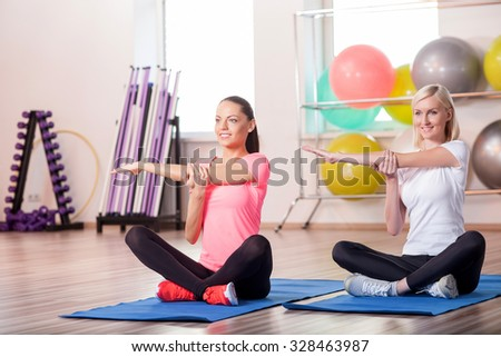 Two beautiful young women are working out at gym. They are sitting and doing exercises. The girls are smiling