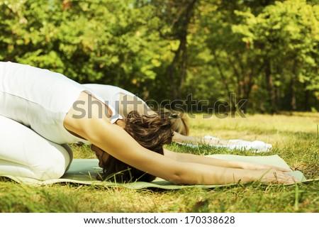 Two beautiful young women doing yoga class in nature. - stock photo