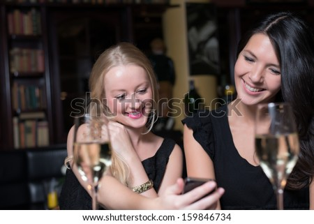 Two beautiful young women enjoying a glass of wine on a night out using their mobile phones laughing at the conversation and text message