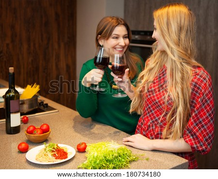 Two beautiful young women friends drinking red wine together in a kitchen - stock photo