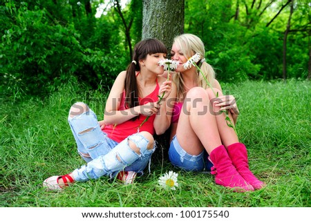 Two beautiful young women friends having fun outdoor. - stock photo