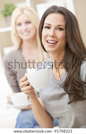 Two beautiful young women friends or girls with perfect smiles drinking tea or coffee from a white cup at home on a sofa - stock photo