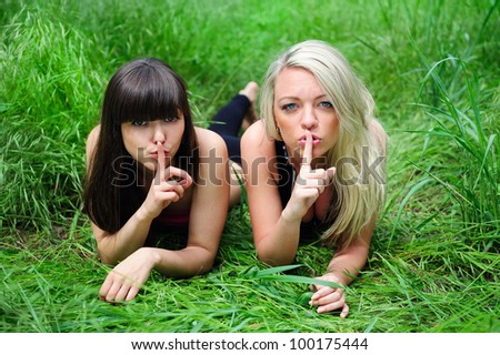 Two beautiful young women friends talking secret. Outdoor. - stock photo