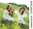 two beautiful young women garlanding flowers in the summer field - stock photo