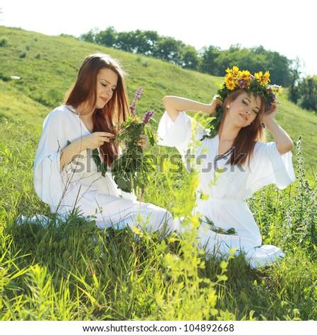 two beautiful young women garlanding flowers in the summer field - stock photo