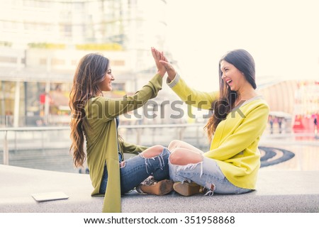 Two beautiful young women giving high five - Pretty girls sitting on a bench outdoors and having fun - Best girlfriends making a promise - stock photo