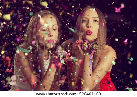 Two beautiful young women having fun at a Christmas party, blowing away confetti and sending kisses. Focus on the girl on the left