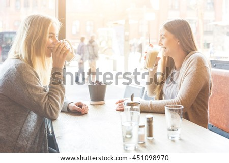 Two beautiful young women in a cafe, drinking coffee and latte macchiato and talking. They are sitting in front of each other, and they are having fun together. Friendship and lifestyle concepts.
