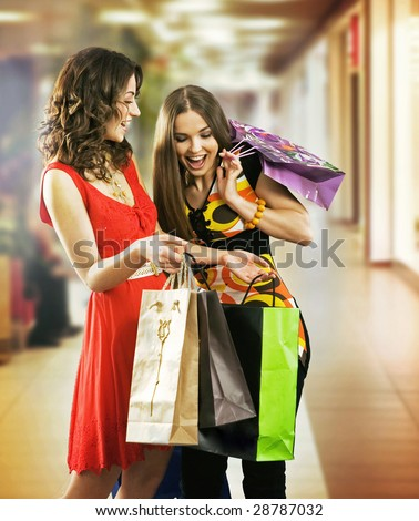 Two beautiful young women in a shopping center checking bags - stock photo