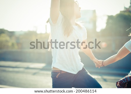 two beautiful young women jumping and dancing in the city - stock photo