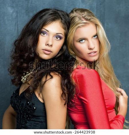 Two beautiful young women on a dark background
