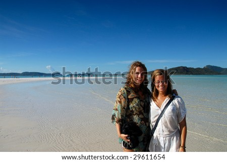Two beautiful young women on paradise beach with blue ocean