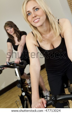 Two beautiful young women, one blond, one brunette, working out on exercise bikes at the gym