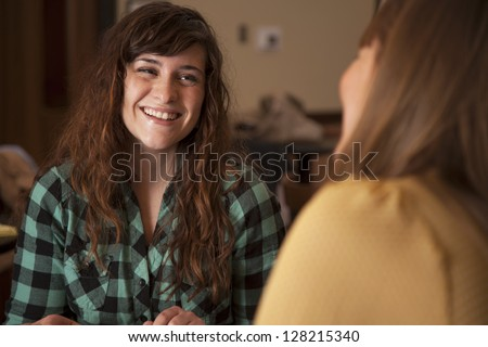 Two beautiful young women sit together and talk. - stock photo