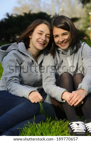 Two Beautiful Young Women Smiling In a Park On a Sunny Day