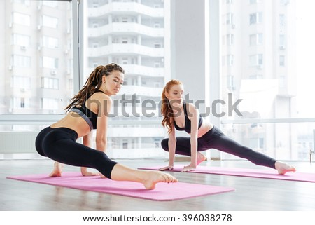 Two beautiful young women stretching legs together in yoga studio - stock photo