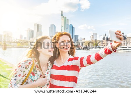 Two beautiful young women taking a selfie with Frankfurt skyline on background on a spring day. They are smiling and looking at the smart phone. Friendship and travel concepts.