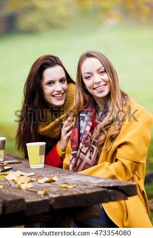 Two beautiful young women talking and enjoying on a sunny autumn day