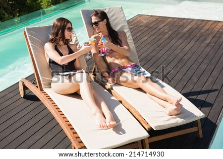 Two beautiful young women toasting drinks by swimming pool - stock photo