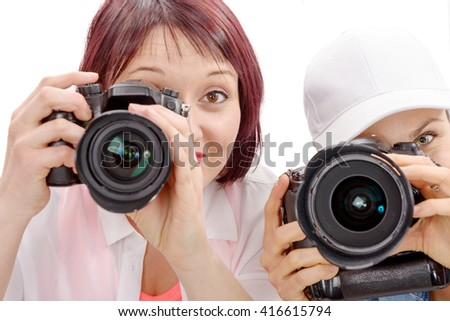 Two beautiful young women using a camera on hwhite background - stock photo