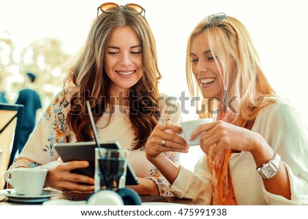 Two beautiful young women using digital tablet.They are having fun in cafe.