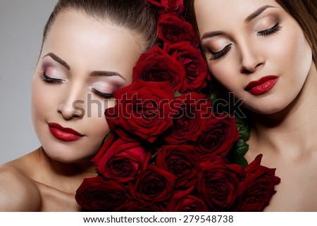 Two beautiful young women with amazing make-up in roses. Cosmetic care, makeup. Sensuality twins. Stylish attractive woman in flowers. Beautiful lady with red lipstick on her lips with eyes closed - stock photo