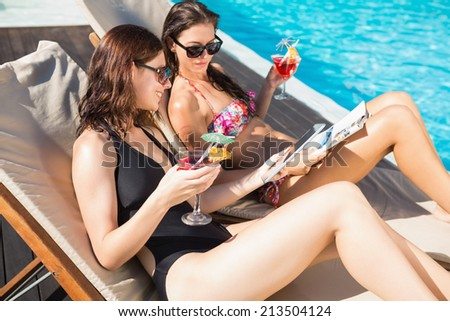 Two beautiful young women with drinks by swimming pool - stock photo