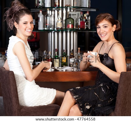 Two beautiful young women with great smile and hairstyle sitting at a bar, drinking coffee, smiling to the camera - stock photo