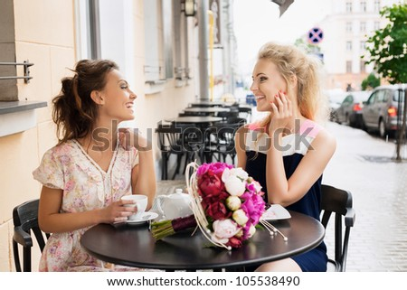 Two beautiful young women with great smile and hairstyle sitting at a bar, drinking tea and coffee. - stock photo