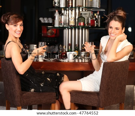 Two beautiful young women with great smile and hairstyle sitting at a bar, drinking water. - stock photo