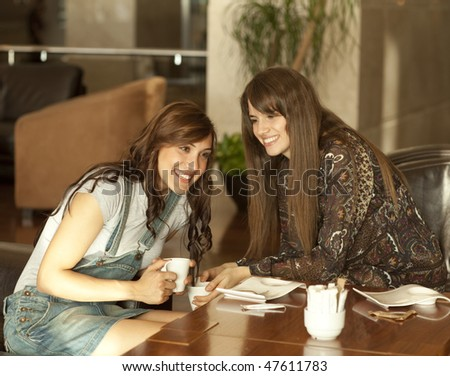Two beautiful young women with great teeth enjoying their lunch break, drinking coffee, sharing a secret. - stock photo