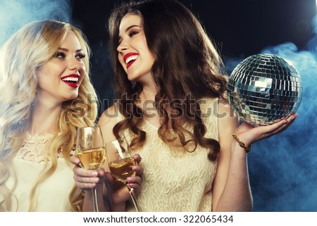 two beautiful young women with wine glasses and disco ball. - stock photo