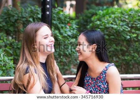Two beauty girlfriends talking on a park bench - stock photo