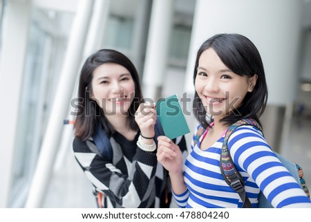 two beauty woman take passport go to travel and smile to you in hong kong airport, asian
