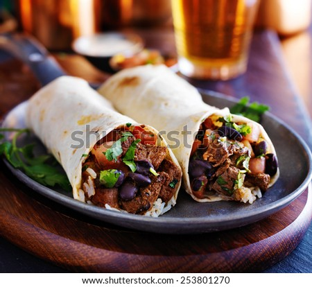two beef burritos with rice, black beans and salsa - stock photo