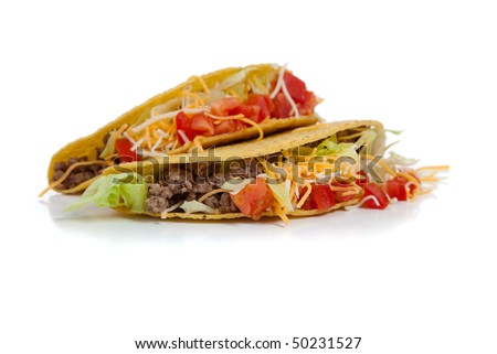 Two beef tacos on corn torillas with beef, lettuce, tomatoes and cheese on a white background with copy space - stock photo