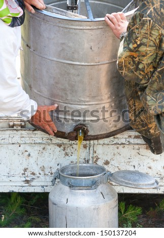 two beekeepers pour honey out from centrifuge