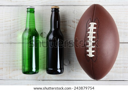 Two beer bottles and an American style football on a rustic whitewashed wood surface. Horizontal format. One green bottle and one brown, both without labels. - stock photo