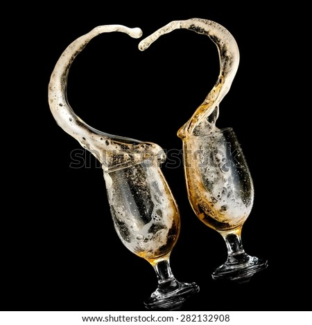 Two beer glasses up in a heart splash - stock photo