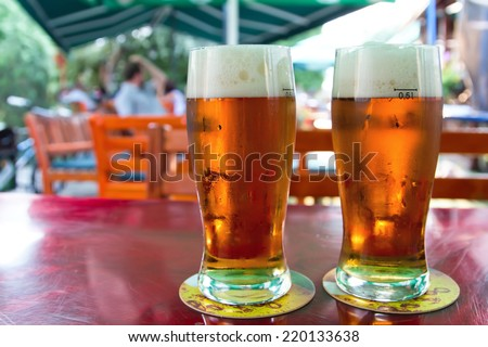 Two beers on table in the garden pub. - stock photo