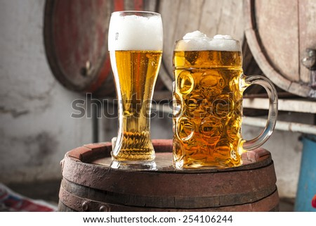 Two Beers with foam and old wood barrels in the background - stock photo