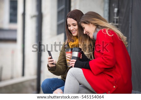 Two best friends are having fun and laughing with smart phone