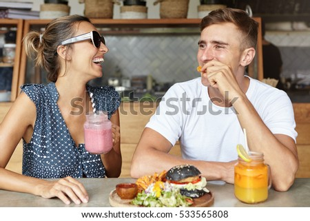 Two best friends having fun together and laughing while eating lunch at coffee shop. Attractive female holding glass of pink smoothie enjoying lively conversation with her handsome boyfriend