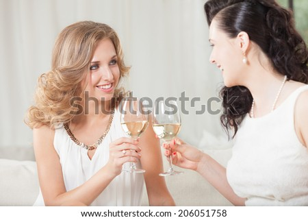 Two best friends having good time with glass of wine - stock photo
