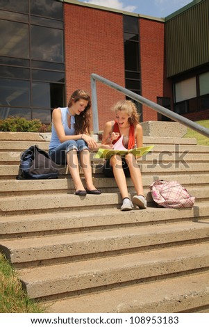 Two best friends sit in the stair of the school