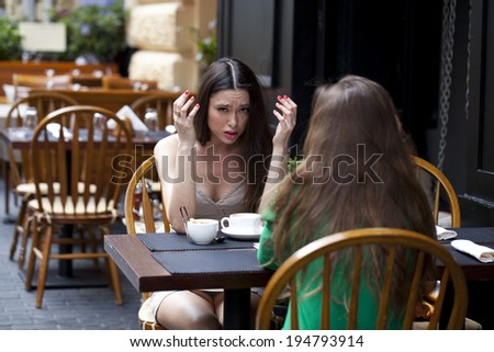 Two best friends solve their problems sitting in cafe - stock photo