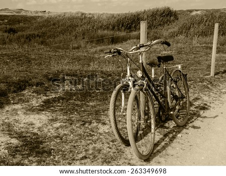 Two bicycles in countryside. Brittany, France. The concept of romance, love and simple everyday life. Aged photo. Sepia.