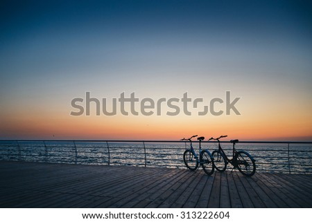 Two bicycles on the beach at sunrise sky - stock photo